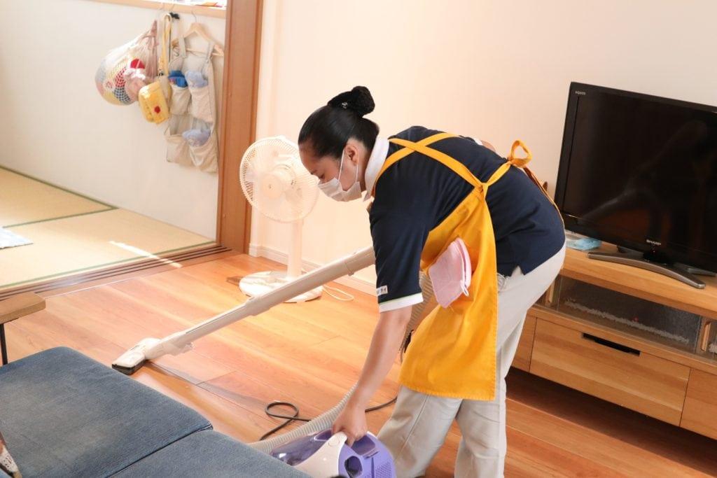 掃除機かけをするサニーメイドサービスのスタッフ