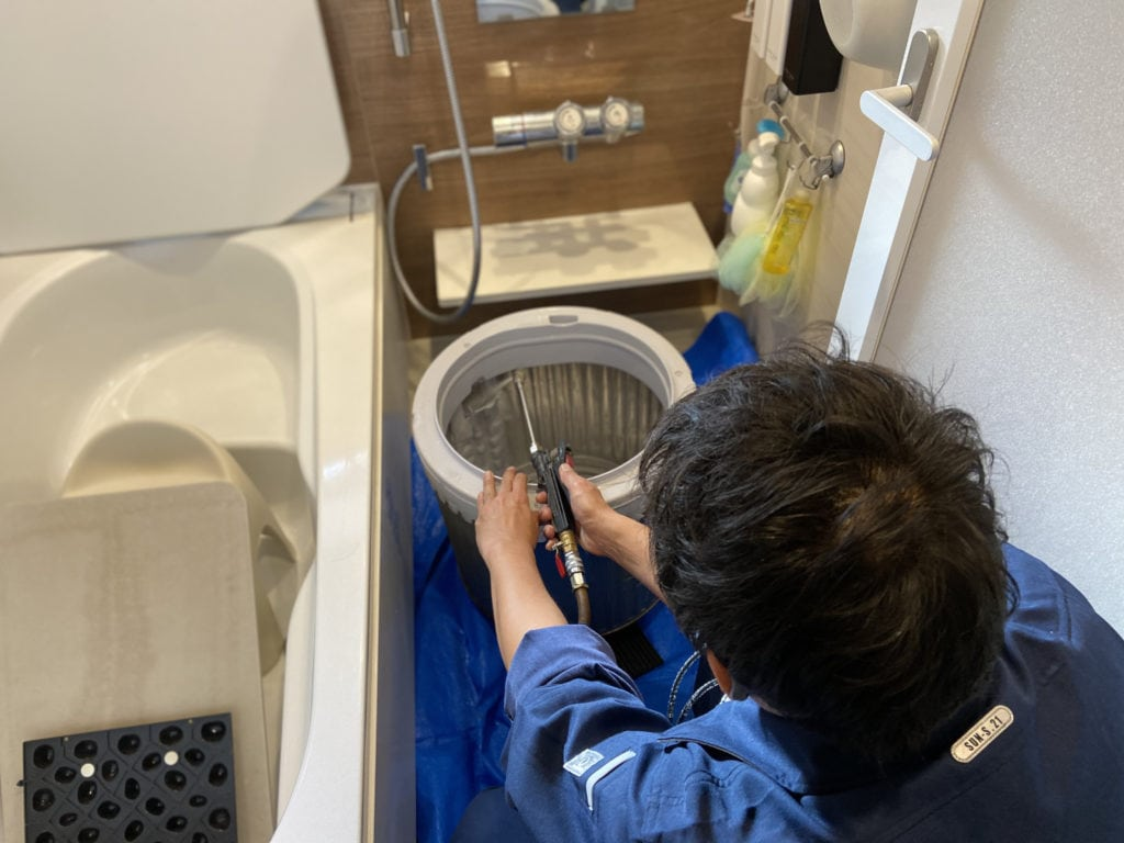 分解したSHARPの穴なし縦型洗濯機の洗濯槽に洗剤を吹きかける様子