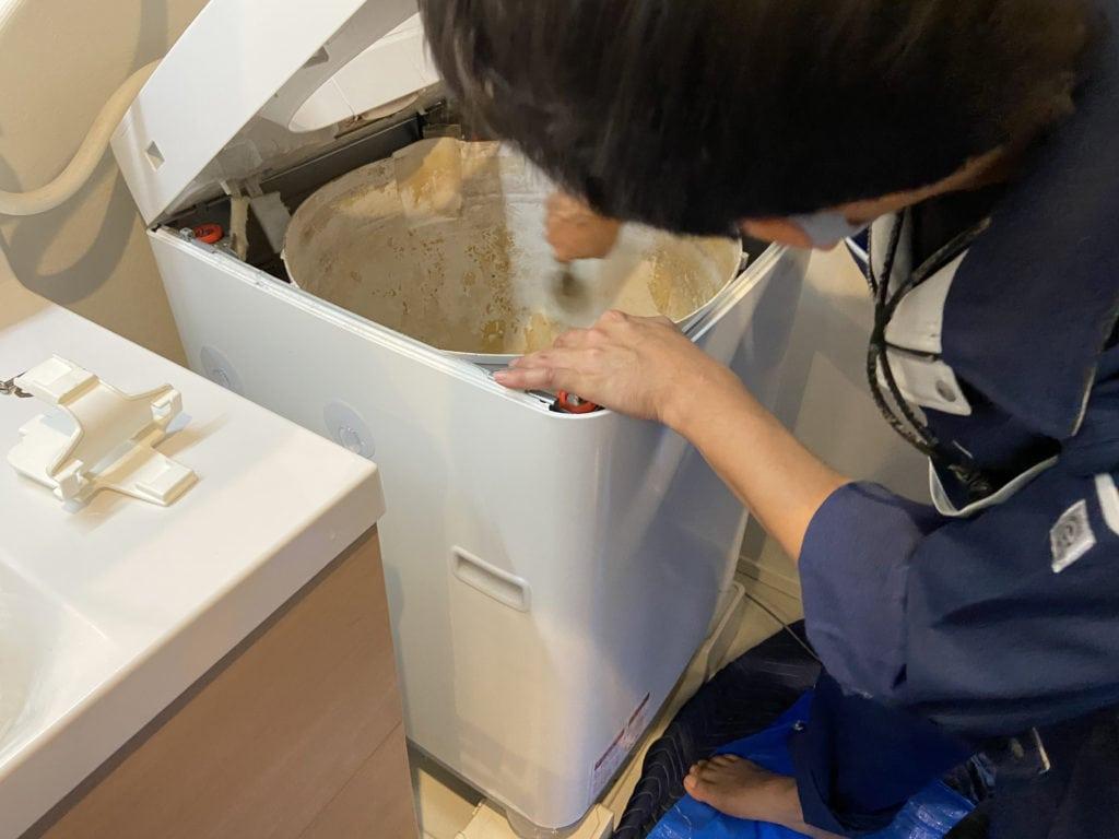 SHARPの穴なし縦型洗濯機のカビ汚れをこする様子