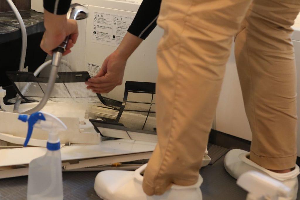 分解したエアコンカバーやフィルターを洗浄するエアコンクリーニング業者