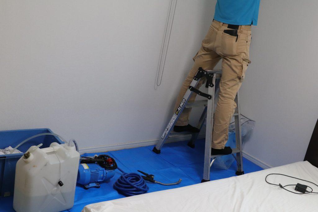 エアコンクリーニングのためにベットを動かして作業するスタッフ