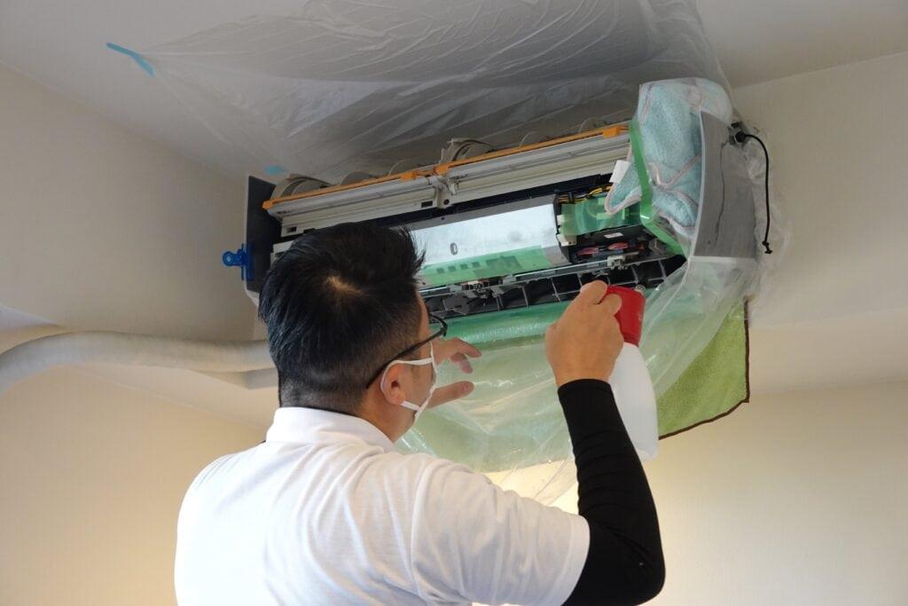 エアコンクリーニング用のエコ洗剤を吹きかける様子