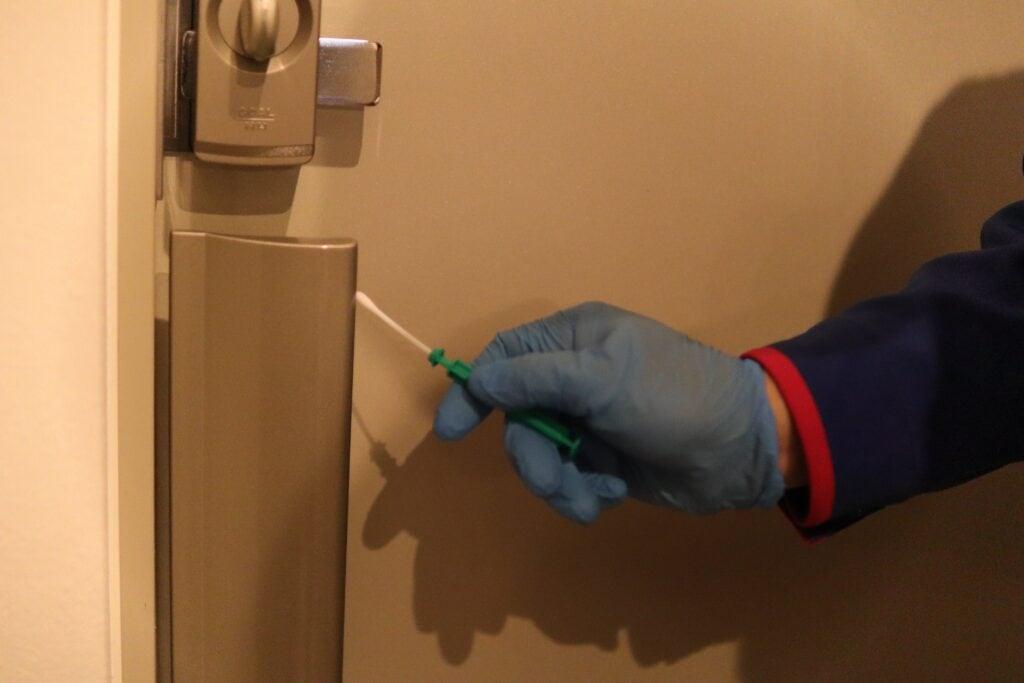 玄関の内ドアノブをルミテスターで計測する様子
