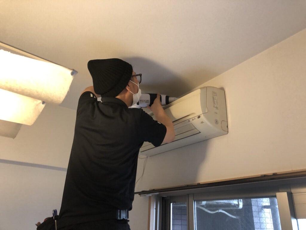 エアコン上部をハンディクリーナーで掃除をする様子