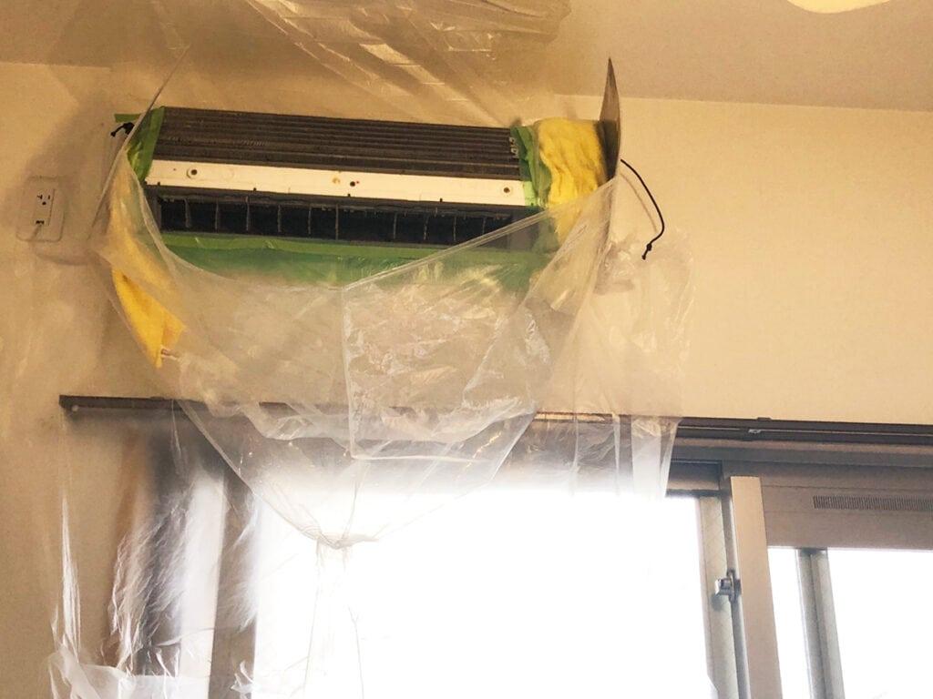 エアコンクリーニングの為に専用カバーで養生をする様子