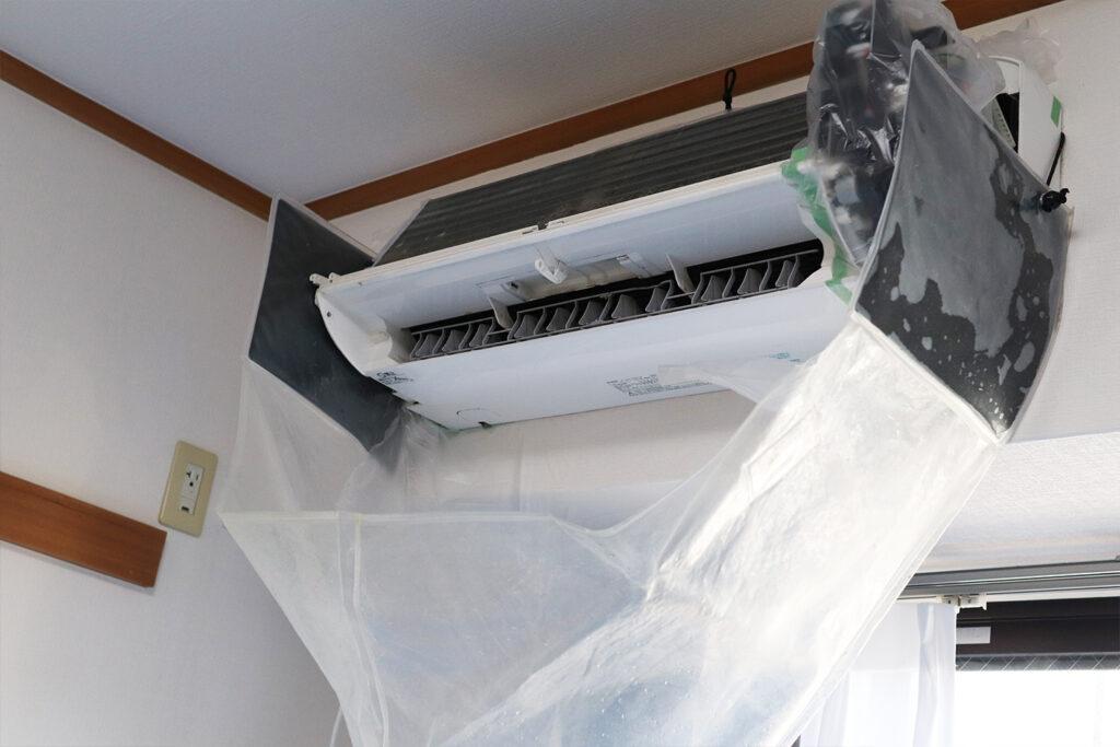 エアコンクリーニング専用のカバーで本体を養生する様子