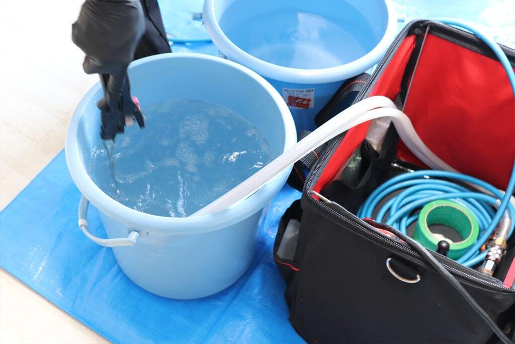 エアコンクリーニングを洗浄する水に塩素系洗剤を混ぜる様子