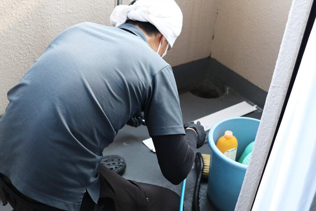 エアコンのパーツをベランダで洗浄する様子