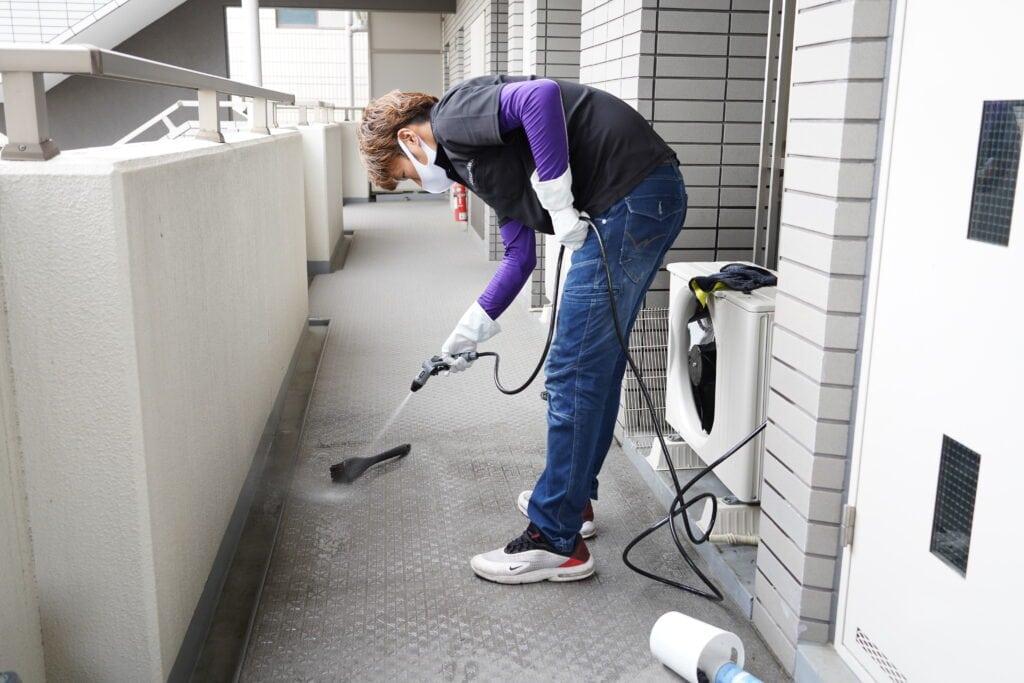 ココナラミーツでのエアコンクリーニング、室外機洗浄後の廊下を掃除する様子